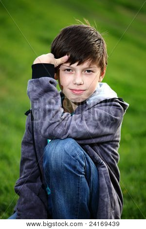 Boy in jeans sits on a grass