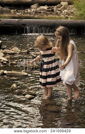 Innocence, purity and youth concept. Girls walk on stones in water stream at waterfall. Children play on sunny summer day on natural landscape. poster