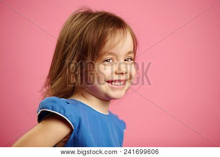 Portrait Of Child Girl Sideways, Expresses Good Mood, Sincere Smiles. Happy Child Isolated On Pink B