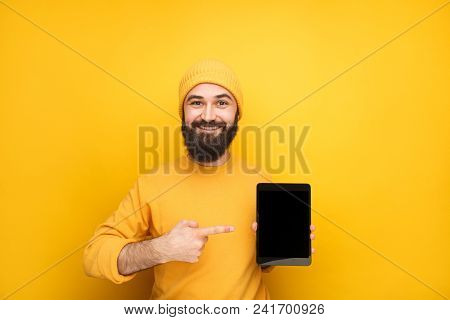 Handsome Bearded Guy In Yellow Hat Holding Modern Touchpad And Pointing At It.