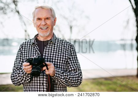 Composition Nuances. Optimistic Senior Man Looking At Camera And Using Camera