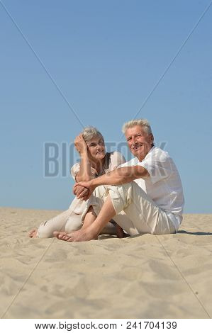 Elderly Couple In Love Sitting On The Sand Together