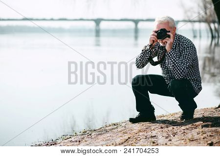 Time To Experiment. Creative Mature Man Sitting Down And Taking Pictures