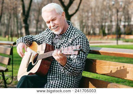 Guitar Player. Cheerful Mature Man Sitting On Bench And Enjoying Guitar Play