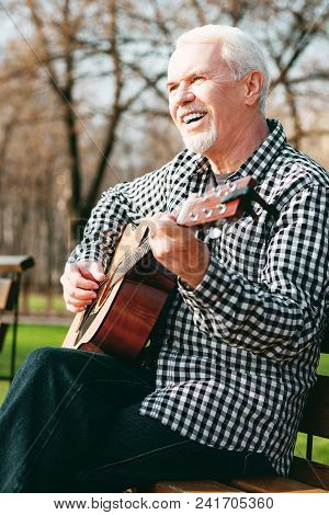 Advantages Of Music. Low Angle Of Exuberant Mature Man Sitting On Bench And Playing Guitar