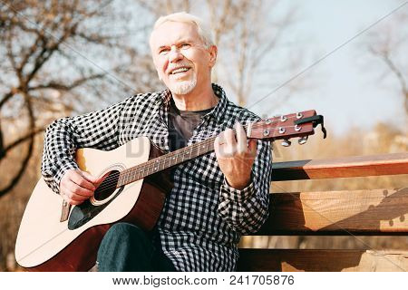 Talented Guitarist. Low Angle Of Joyful Mature Man Sitting On Bench And Playing Guitar