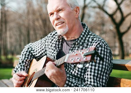Basic Chord. Inspired Mature Man Posing In Park And Playing Guitar