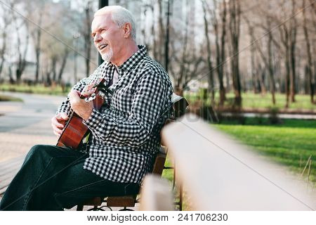 Master Guitar. Appealing Mature Man Learning Song And Playing Guitar