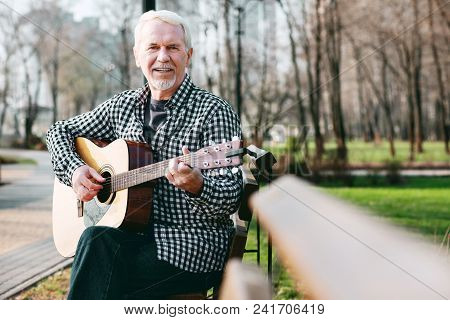 Master Chord. Nice Mature Man Looking At Camera And Playing Guitar