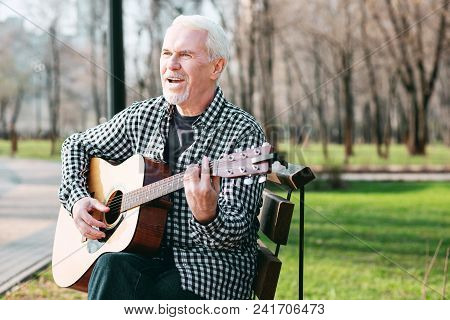 Guitar As Hobby. Handsome Mature Man Chanting And Playing Guitar