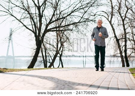 Nice Weather. Optimistic Senior Man Running And Enjoying Nature