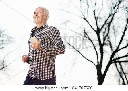 Alone With Nature. Low Angle Of Energetic Senior Man Listening To Music And Enjoying Nature