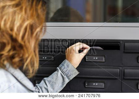 Woman Inserting Letter In A House´s Mailbox