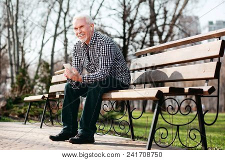 Audio Book. Low Angle Of Enthusiastic Senior Man Posing On Bench And Listening To Music
