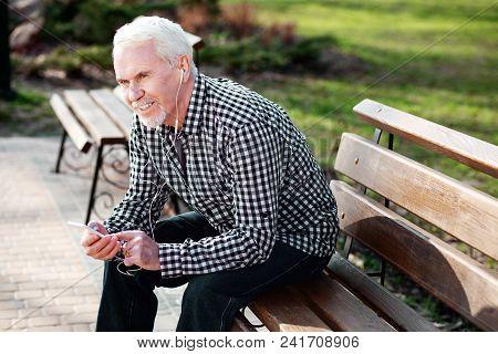 Music Outdoors. Vigorous Senior Man Resting On Bench And Listening To Music
