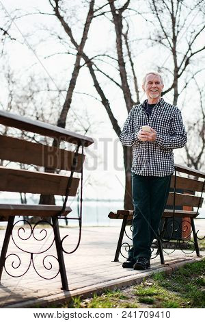 Place For Music. Low Angle Of Reflective Senior Man Staying In Park And Listening To Music
