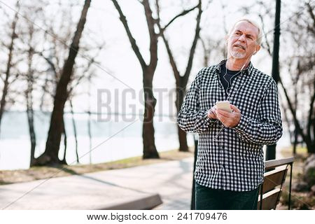 Digital Music. Pleased Senior Man Leaning On Bench And Listening To Music