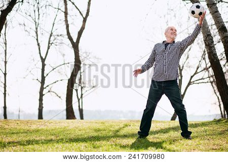 Ball Game. Joyful Mature Man Exercising With Ball And Staying On Grass