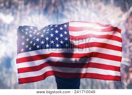 Patriotic holiday. Happy young man with American flag looking at fireworks. USA celebrate 4th of July.