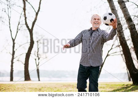Ball Sport. Optimistic Mature Man Exercising With Ball And Smiling