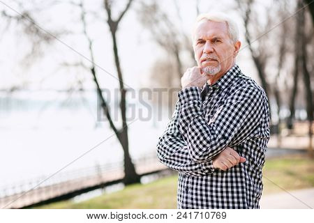 Way Out. Reflective Senior Man Standing In Park And Touching Face