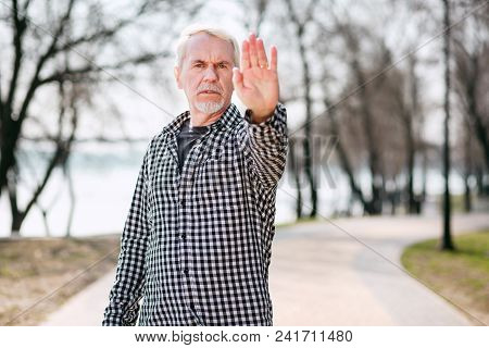 Not Allow. Serious Senior Man Standing In Park And Showing Hand