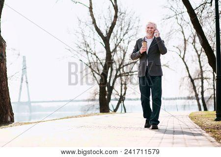 Lunch Break. Jolly Senior Businessman Walking In Park And Talking On Phone
