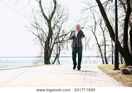 Agreeable Conversation. Gay Senior Businessman Strolling In Park And Talking On Phone