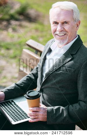 Outside Office. Jovial Mature Businessman Using Laptop While Looking At Camera