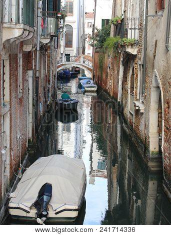 Many Houses Near The Narrow Water Way And Many Boats In Venice Italy