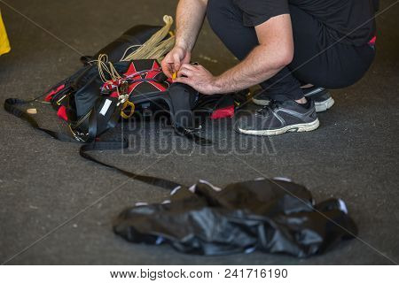 Skydiver Packing His Black Parachute In The Aerodrome Room