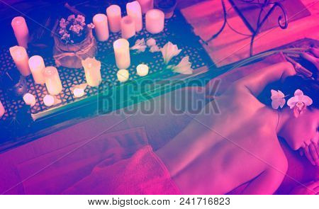Massage of woman in spa salon. Top view of girl on candles background therapy room. Luxary interior in oriental therapy salon. Colorful toning.