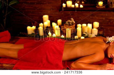 Massage of woman in spa salon. Girl on candles background in therapy room. Luxary interior in oriental therapy salon. Female have relax after sport. Close up of back body part and stack towels.