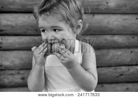 Kids Playing With Toys. Cute Little Boy Blond In White Pinafore Eats Two Green Apples On Summer Day