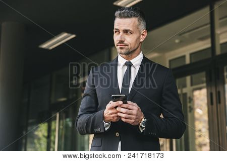 Portrait of a handsome young businessman dressed in suit standing outside a glass building and holding mobile phone
