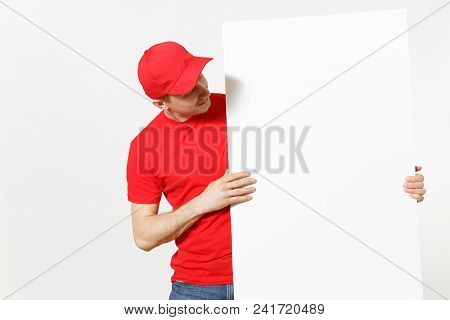 Delivery Young Man In Red Uniform Isolated On White Background. Male Courier In Cap, T-shirt Holding