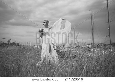 Sensual Woman. Thoughtful Sensual Young Bride In Wedding Dress With Train Holding Coral Bouquet Of A
