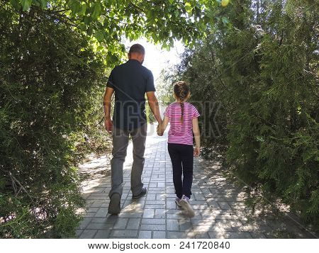 Dad And Daughter Are Walking In The Park