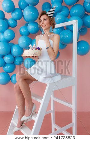 A Young Woman Makes A Wish With Birthday Cake Sitting On White Ladder, Blue Shiny Balls On Backgroun