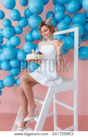 Beautiful Happy Girl Holding Birthday Cake With Candles And 20 Numbers. Sitting On White Ladder In P