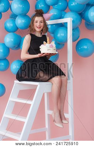 Happy Teen Girl Holding Unicorn Layered Cake Decorated With Meringues. Pink Background With Blue Bal