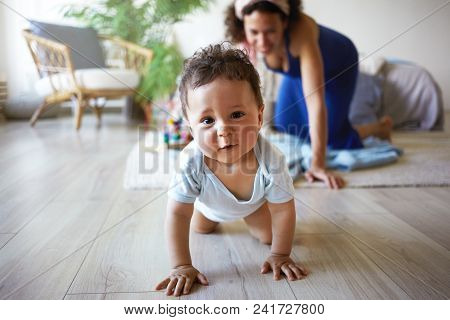 Horizontal Shot Of Cute Funny Infant Crawling Along Floor From His Mother Who Is Standing On Her Kne