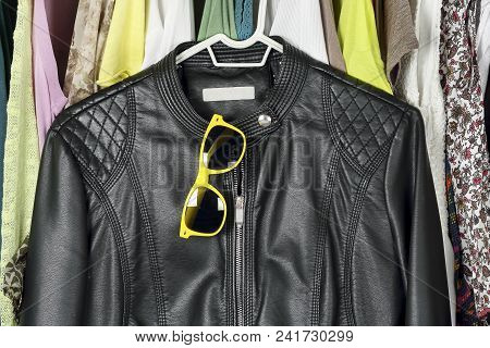 Black Leather Jacket And Sunglasses In Front Of Other Female Clothing