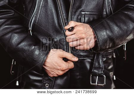 Fastens The Lock On A Black Leather Jacket With Zipper Close-up