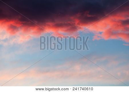 Beautiful Sky Background With Dark Blue, Red Stormy Cloud At The Top And Light Blue, Pink Sky At The