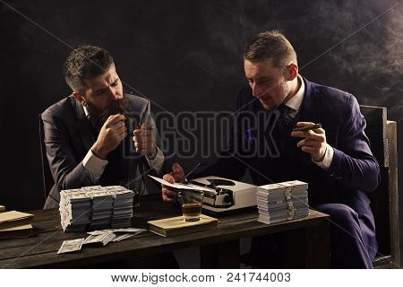 Elegant Man In Suit. Men Sitting At Table With Piles Of Money And Typewriter. Company Engaged In Ill