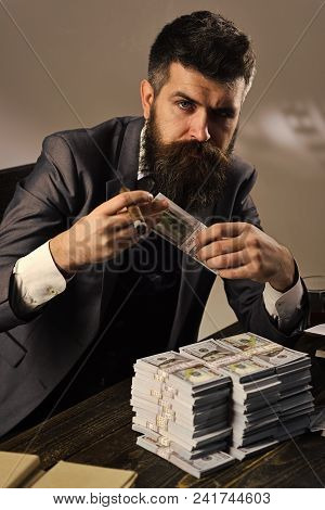 Elegant Man In Suit. Man Sitting At Table With Piles Of Money, Counting Profit. Illegal Cash Concept
