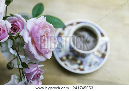 Flowers. Roses. Bacground image. Flowers and coffee cup background space for text. Roses flowers background wooden table. Pink roses and coffee cup background with space for text. Background. Flowers. Coffee cup. Flower. Pink roses and black coffee. Flowe