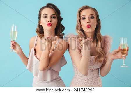 Two lovely women in dresses posing with glasses of champagne and sends air kisses at camera over turquoise background