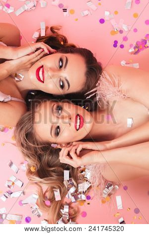 Vertical photo of shining girls at carnival smiling and lying on the floor with heads in opposite directions under falling colorful sequins or confetti isolated over pink background